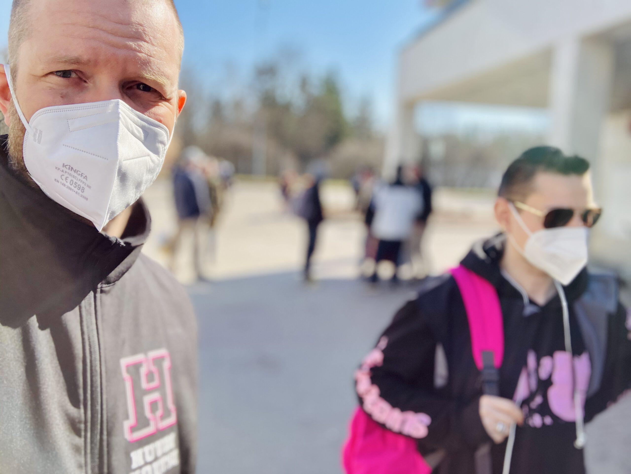Kaksi miestä maskit naamalla Huudikoutsihuppareissa kävelevät kadulla