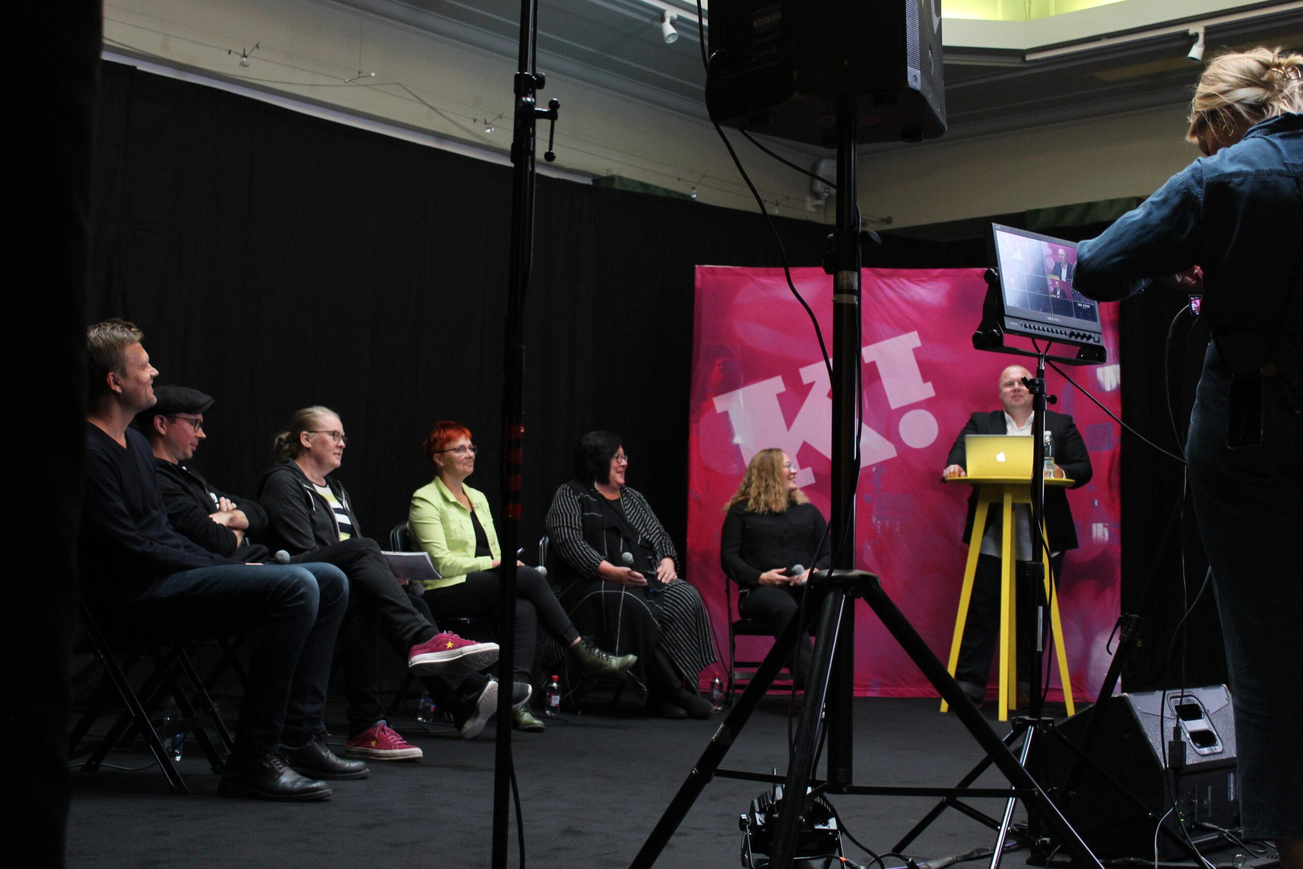Etualalla striimin kuvausvälineitä ja taka-alalla ihmisiä istumassa mikrofonien kanssa