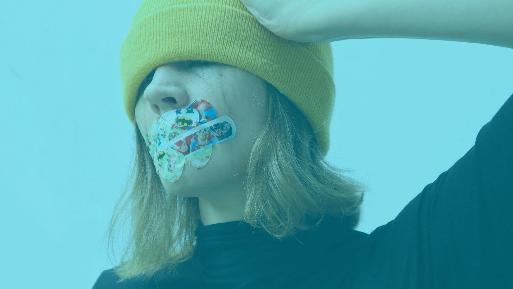 Nainen keltainen pipo päässä. Pipo on silmillä ja naisen suun edessä on laastareita. Hän pitää kädellä kiinni päästään.